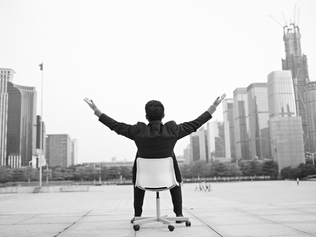 asian businessman opens arms embracing the city, black and white. photo