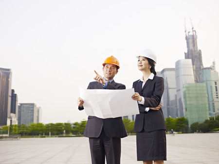hard: asian business people with safety hats and blueprint.