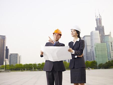 arquitecto: Hombres de negocios asiáticos con sombreros de seguridad y modelo. Foto de archivo