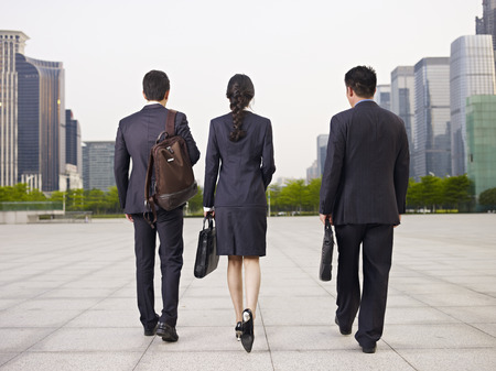rear view of three business people walking on street.
