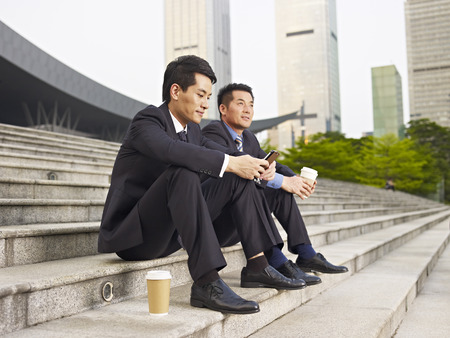 asian businessmen sitting on steps and talking. photo