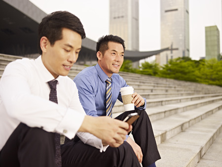 man drinking coffee: asian businessmen sitting on steps and talking. Stock Photo