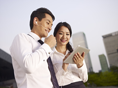 earphone: young asian man and woman looking at tablet computer.