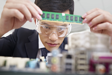 young asian man fixing computer with protective eyewear Stock Photo