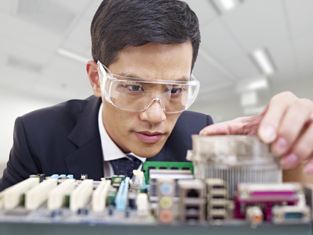 young asian man fixing computer with protective eyewear photo