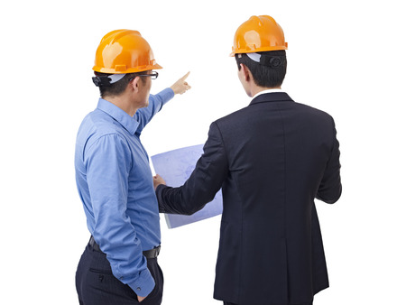 hard hats: asian businessmen with safety helmet and blueprint, rear view.