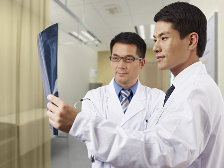 two asian doctors looking at x-ray film in consultation room. photo