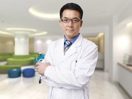 healthcare asian: portrait of a male asian doctor in hospital lobby.