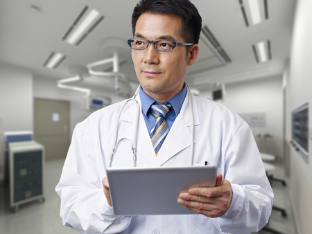 healthcare worker: male asian doctor with tablet computer. Stock Photo