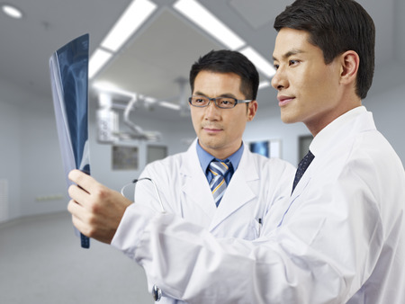 medical school: two asian doctors looking at x-ray film.