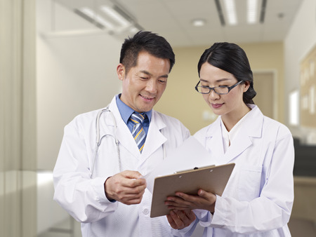 healthcare worker: two asian doctors having a discussion.