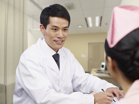 young male doctor: doctor and nurse having a conversation in office.