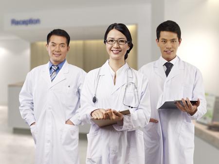 asian medical team standing in hospital lobby.