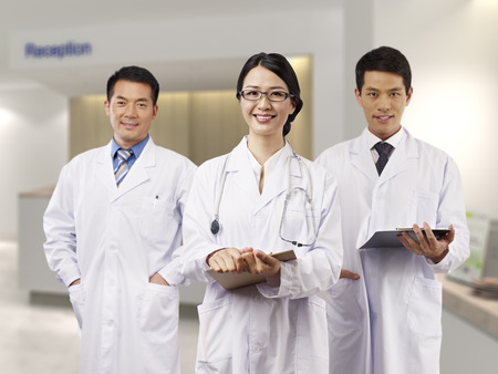 korean man: asian medical team standing in hospital lobby.