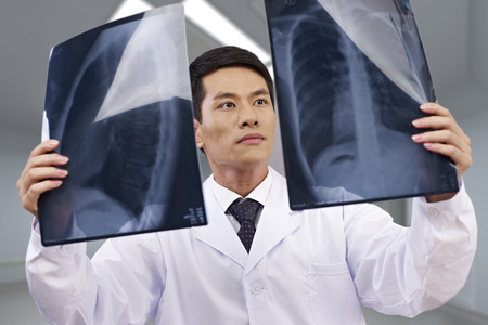 asian doctor looking at x-ray films. Stock Photo