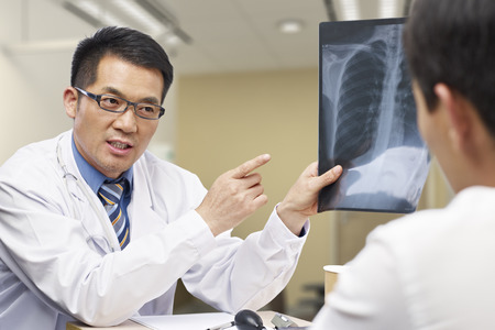 consult: asian doctor talking to patient about x-ray result. Stock Photo