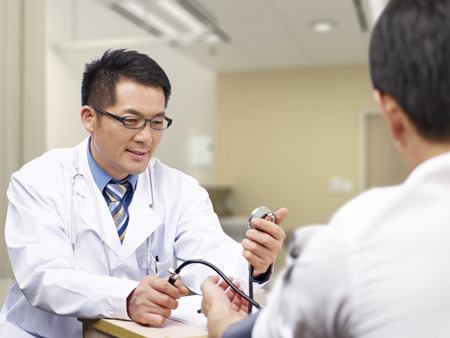 outpatient: asian doctor measuring blood pressure of a patient.