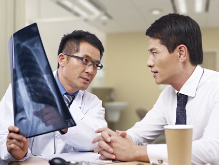 outpatient: asian doctor talking to patient about x-ray result. Stock Photo