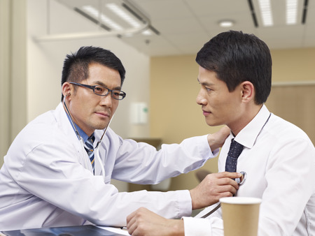 asian doctor checking patient with stethoscope.
