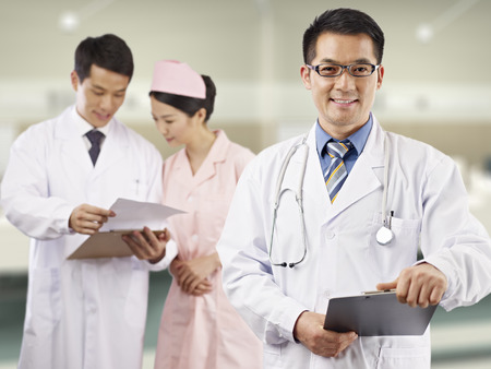 hospital gown: portrait of an asian medical team. Stock Photo