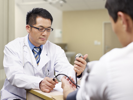 hypertension: asian doctor measuring blood pressure of a patient.