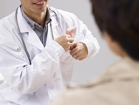 doctor putting money: asian doctor putting kickback money in pocket. Stock Photo