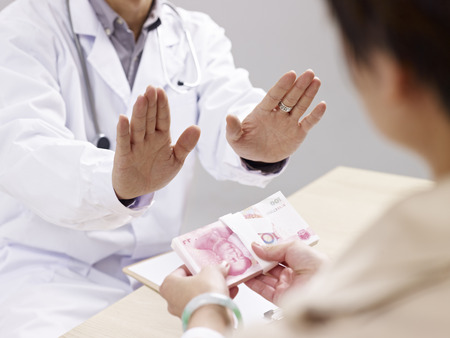 refusing: asian doctor refusing kickbacks or bribes.