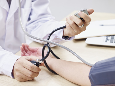 check up: doctor measuring blood pressure of a patient. Stock Photo