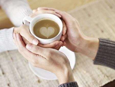tomados de la mano: manos de los j�venes amantes que sostienen una taza de caf�.