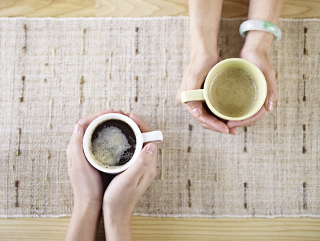 two people talking while drinking coffee.