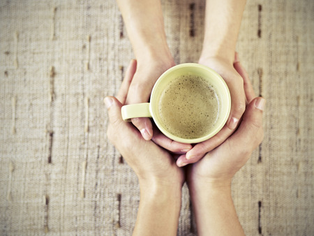 both: hands of young lovers holding a cup of coffee.