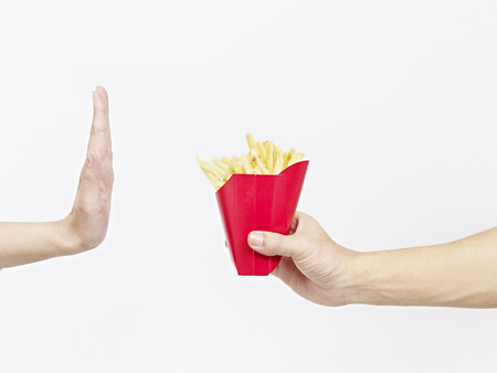 high calorie foods: man refusing a pack of french fries. Stock Photo