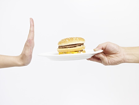 high calorie foods: man refusing a hamburger. Stock Photo