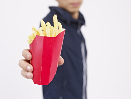 high calorie foods: man holding a pack of french fries.