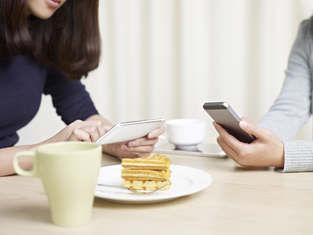 having a break: women using cellphones while having tea break.