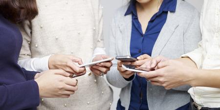 一緒に携帯電話を使用している人々 の小さなグループ。