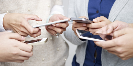 medios de comunicaci�n social: peque�o grupo de personas que utilizan tel�fonos celulares juntos. Foto de archivo