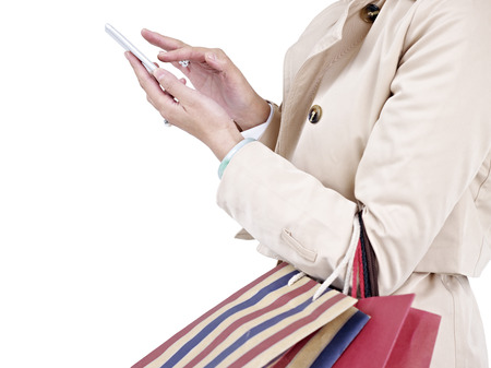 dialing: woman with shopping bags using cellphone. Stock Photo
