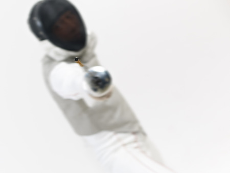 fencing foil: male asian fencer in action