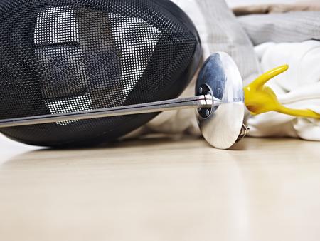 rapier: fencing mask and rapier on floor.