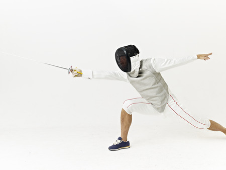 attacking: a male fencer attacking opponent.