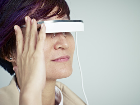 wearable: woman looking into a wearable device with head-mounted display.