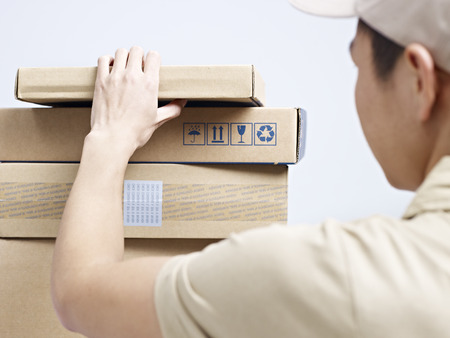 courier delivery: male asian courier company worker checking packages to be delivered. Stock Photo