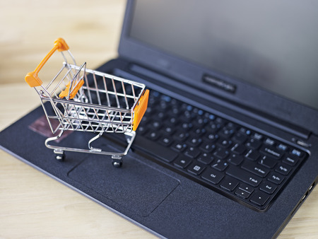 toy shopping cart on top of laptop keyboard. photo