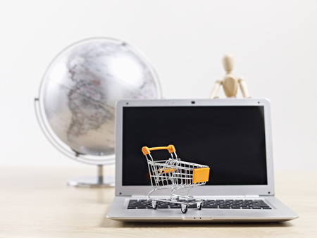 placing: toy shopping cart on top of laptop computer with wooden dummy and world globe in background. Stock Photo