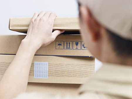 deliveryman: male asian delivery man checking packages to be delivered. Stock Photo