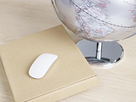 computer mouse on top of carton box next to world globe. photo