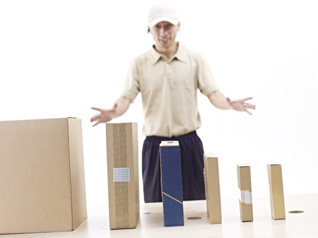 warehouseman: carton boxes lined up on table with uniformed man in background.