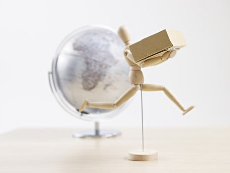 wooden dummy carrying cardboard box with globe in the background, global logistics concept. photo