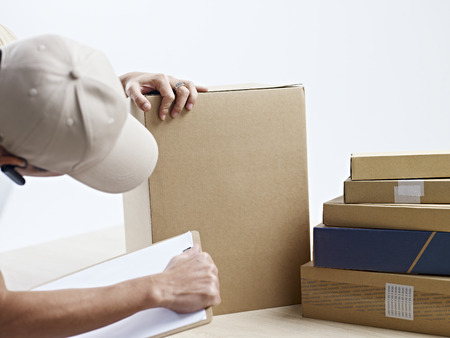 moving company: male warehouse worker checking and recording packages received. Stock Photo